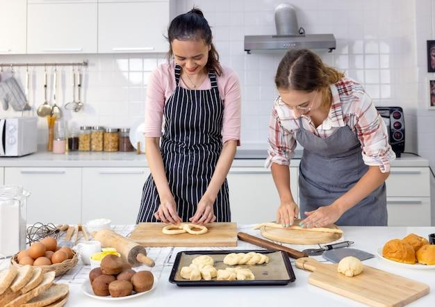 Dans la maison de kat, une femme magnifique et souriante et son amie font du pain ensemble.