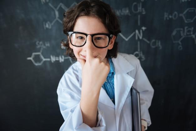 Sûr dans mon succès. scientifique intelligent confiant optimiste debout près du tableau noir dans le laboratoire tout en profitant de cours de médecine et en touchant ses lunettes