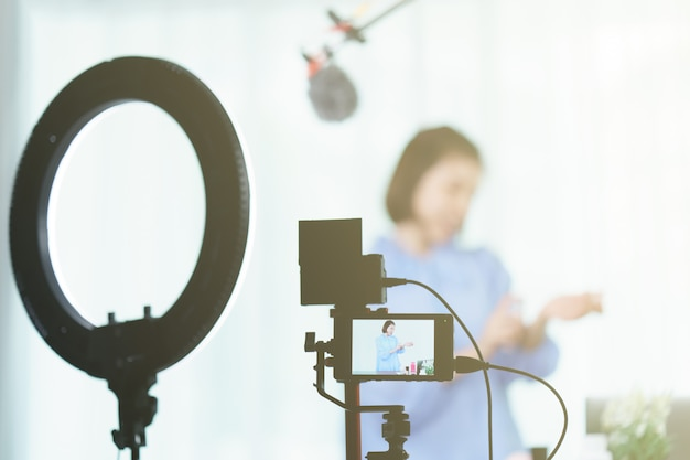 Dans monitor woman vlogger tenant le parfum dans les mains, pendant l'enregistrement vidéo pour le blog.
