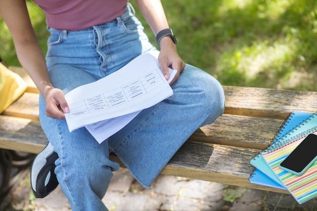 Dans le parc. une fille dans un t-shirt rose tenant assis sur le banc dans le parc