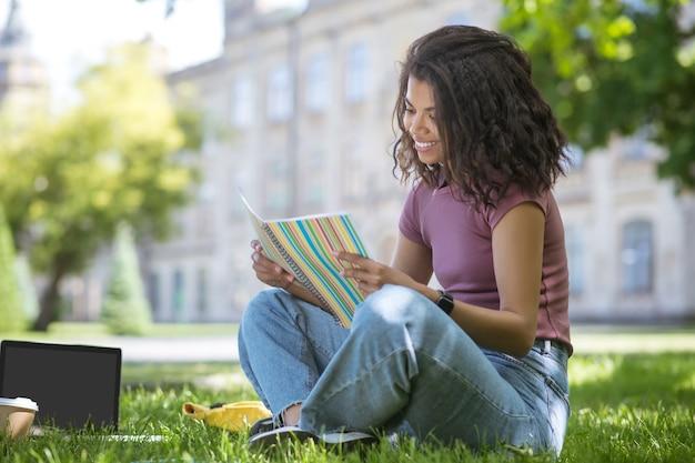 Dans le parc. une jolie fille en t-shirt rose assise sur l'herbe dans le parc et étudiant