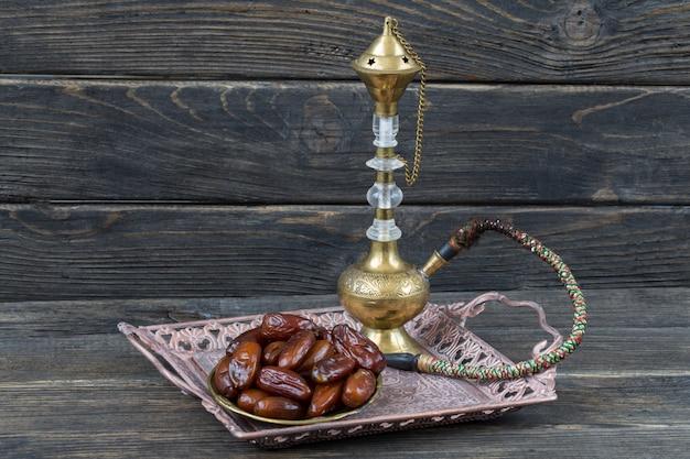 Dans une plaque de bronze dates et narguilé. kareem ramadan.
