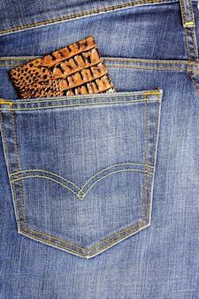 Dans la poche d'un jean bleu foncé, cache passeport en cuir de reptile