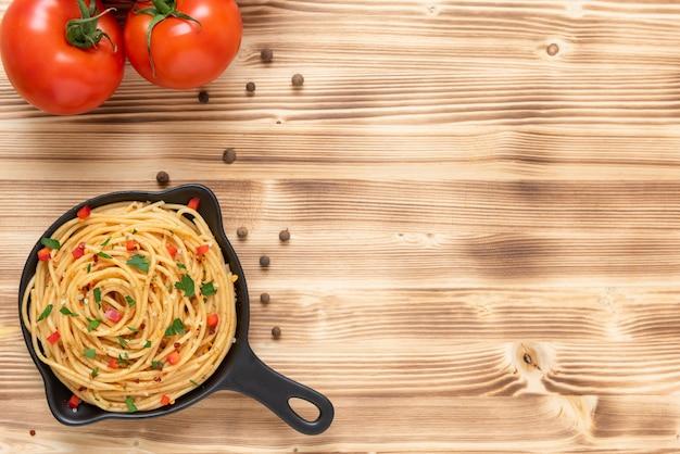 Dans une poêle, vermicelles aux assaisonnements et tomates. copiez l'espace.