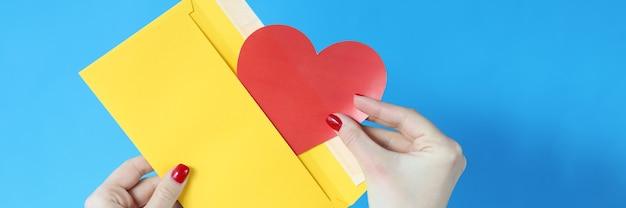 Dans sa main, il y a une enveloppe jaune et un concept de félicitations romantiques coeur rouge