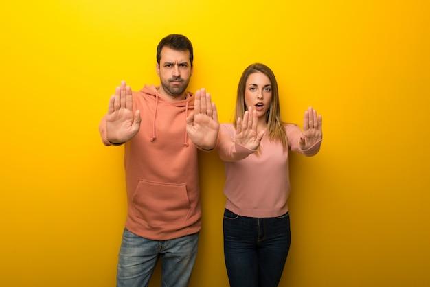 Dans la saint valentin groupe de deux personnes sur fond jaune faisant un geste d'arrêt pour déçu par un avis