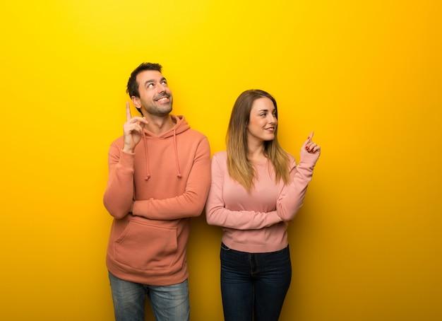 Dans la saint valentin groupe de deux personnes sur fond jaune pointant une bonne idée et levant les yeux