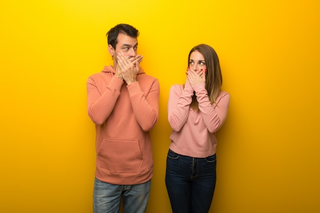 Dans la saint valentin groupe de deux personnes sur fond jaune se couvrant la bouche avec les mains pour avoir dit quelque chose d'inapproprié