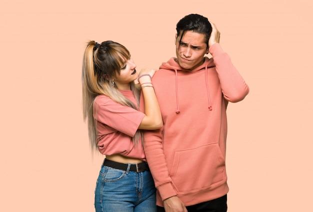 Dans la saint valentin jeune couple ayant des doutes en se gratifiant la tête sur fond rose