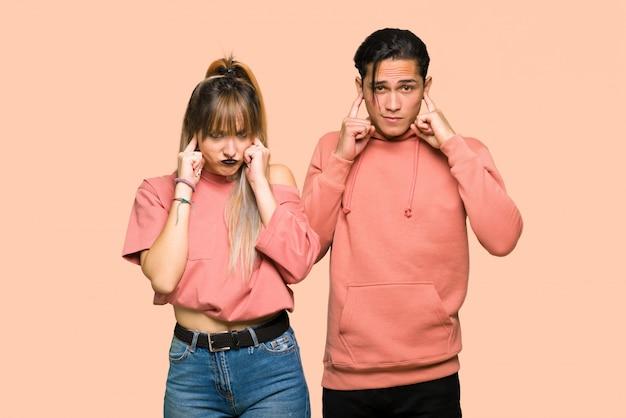 Dans la saint valentin jeune couple couvrant les deux oreilles avec les mains sur fond rose