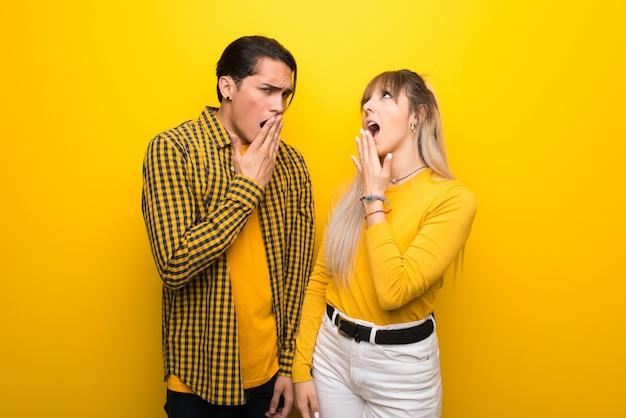 Dans la saint valentin jeune couple sur fond jaune vibrant bâillant et couvrant bouche grande ouverte avec la main