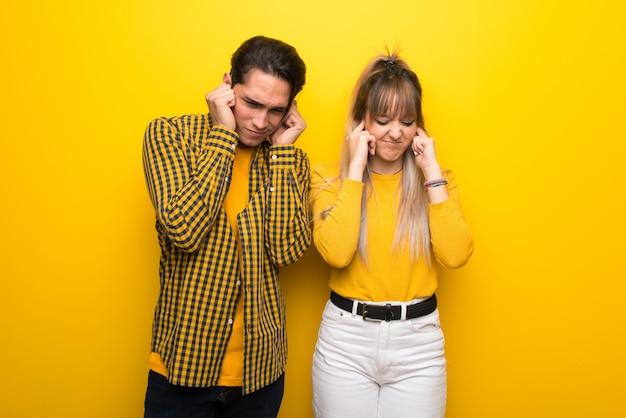 Dans la saint valentin jeune couple sur fond jaune vibrant couvrant les oreilles avec les mains. expression frustrée