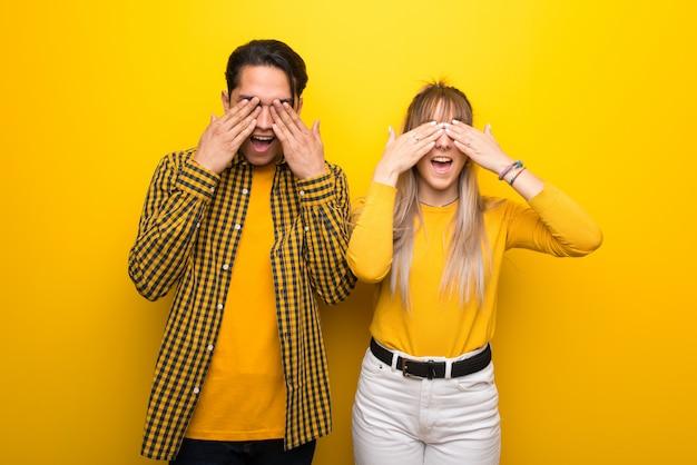 Dans la saint valentin jeune couple sur fond jaune vibrant couvrant les yeux par les mains. surpris de voir ce qui nous attend