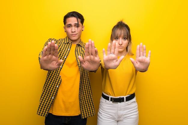 Dans la saint valentin jeune couple sur fond jaune vif faisant arrêt geste pour déçu par un avis