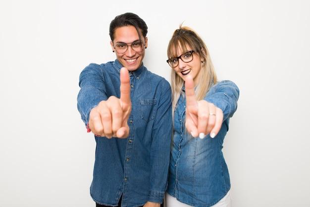 Dans la saint valentin jeune couple avec des lunettes montrant et en levant un doigt