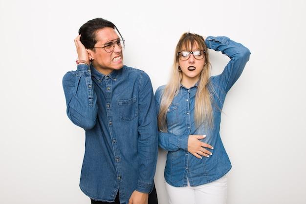 Dans la saint valentin un jeune couple avec des lunettes prend les mains sur la tête à cause de la migraine