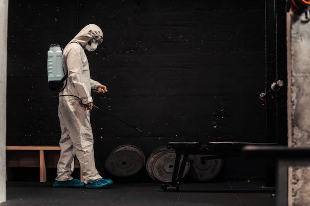 Dans la salle de sport isolée préventivement, une personne vêtue d'une combinaison de protection spéciale rafraîchit et nettoie l'air
