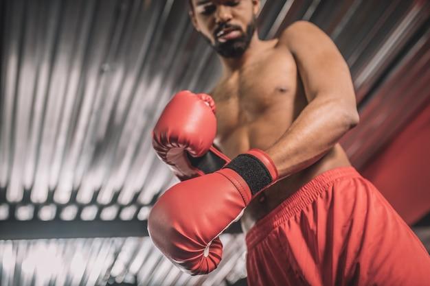 Dans une salle de sport. kickboxer à la peau foncée en short rouge et gants de boxe rouges