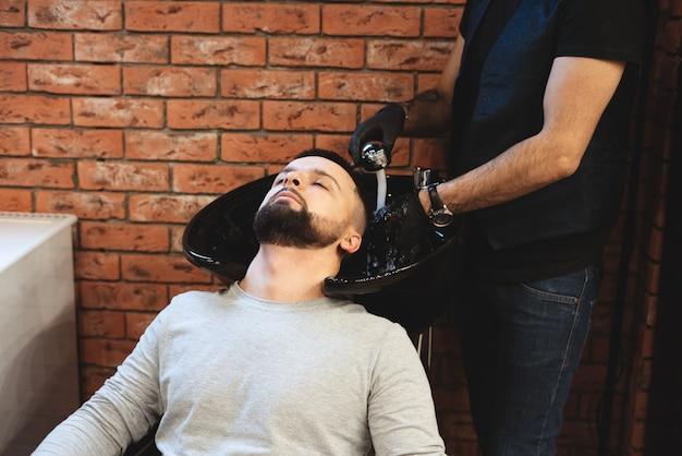 Dans un salon de coiffure, un homme se lave les cheveux.