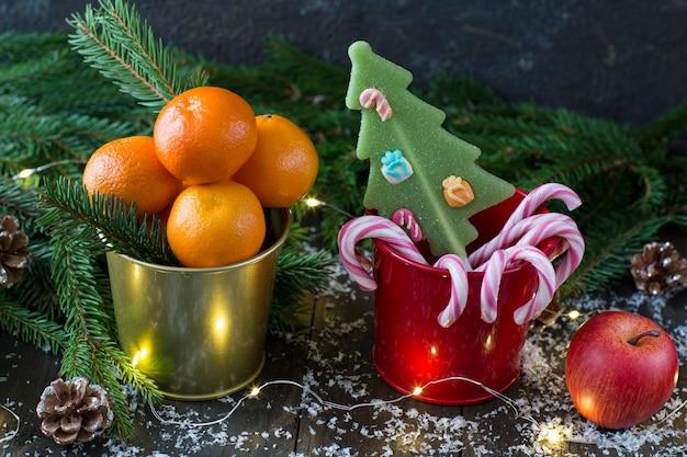 Dans un seau mandarines, dans un seau rouge de bonbons, une pomme rouge, des branches d'épinette, des cônes