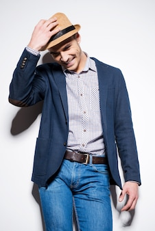 Dans son propre style. beau jeune homme en tenue décontractée intelligente ajustant son fedora et souriant tout en se tenant contre un mur