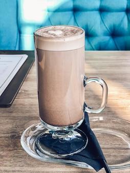 Dans une tasse en verre de cacao, une boisson avec un coeur de lait fouetté sur une table dans un restaurant. photographie de boissons au café.