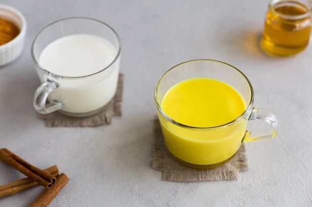 Dans une tasse en verre, du lait ordinaire, dans l'autre, du lait doré une boisson chaude indienne avec de la poudre de racine de curcuma. à côté se trouvent les ingrédients du curcuma, du miel et des bâtons de cannelle. fond gris.