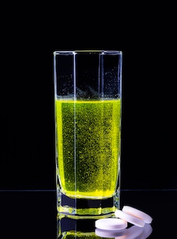 Dans une tasse en verre, un grand comprimé blanc contenant de la vitamine c se dissout dans l'eau sur fond noir