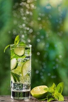 Dans un verre une boisson d'été rafraîchissante au concombre et au citron vert, de grosses bulles de gaz