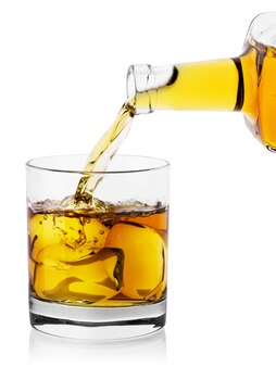 Dans un verre avec de la glace s'écoule d'une bouteille de whisky de malt