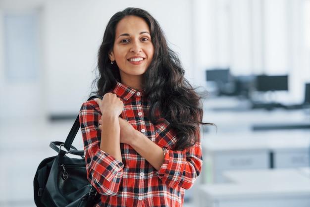 Dans des vêtements décontractés. portrait de jeune femme séduisante debout au bureau avec sac noir
