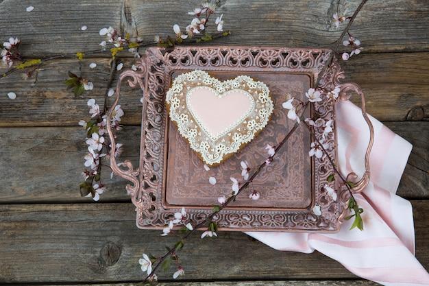 Dans une vieille plaque de bronze en pain d'épice en forme de coeur et une branche de cerisier en fleurs