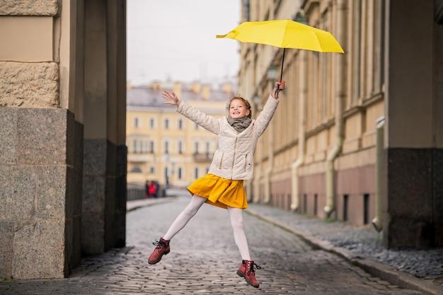 Dans une vieille rue de la ville, une fille en robe jaune avec un parapluie jaune rotait joyeusement.