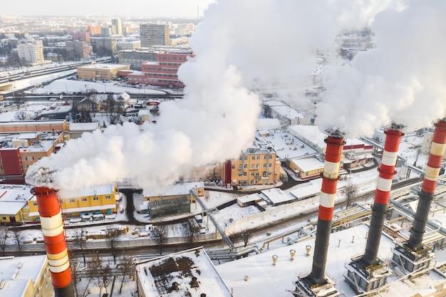 Dans la ville d'hiver, les cheminées de l'usine fument. le concept de pollution atmosphérique. pollution de l'environnement par les déchets industriels.