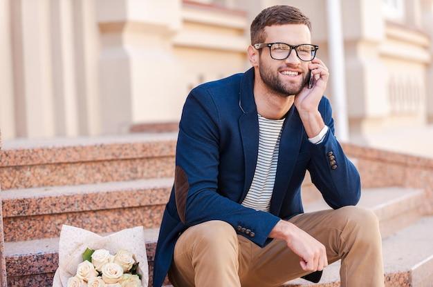 Dans votre attente! beau jeune homme en veste intelligente parlant au téléphone portable et souriant assis sur l'escalier avec un bouquet de roses posé près de lui