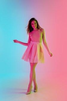 Dansant. belle fille séduisante en tenue à la mode et romantique sur fond rose-bleu dégradé à la lumière du néon. portrait en pied. copyspace pour l'annonce. concept d'été, de mode, de beauté, d'émotions.