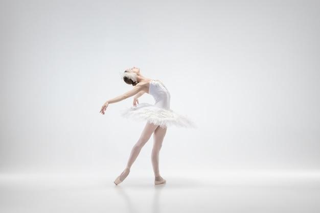 Danse de ballerine classique gracieuse isolée sur fond de studio blanc. femme en vêtements tendres comme un cygne blanc. le concept de grâce, d'artiste, de mouvement, d'action et de mouvement. ça a l'air en apesanteur.