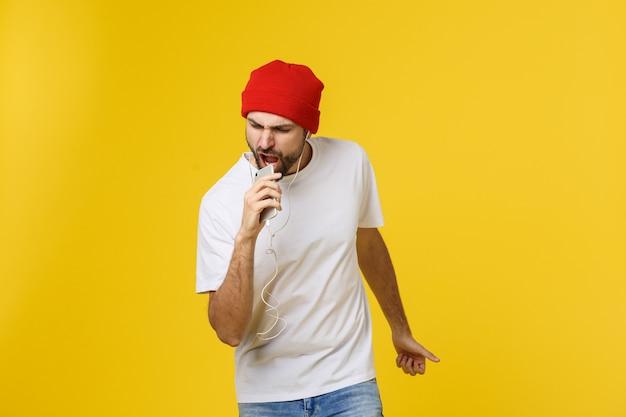 Danse. beau jeune homme élégant dans des écouteurs tenant un téléphone portable et dansant en se tenant debout contre le jaune.