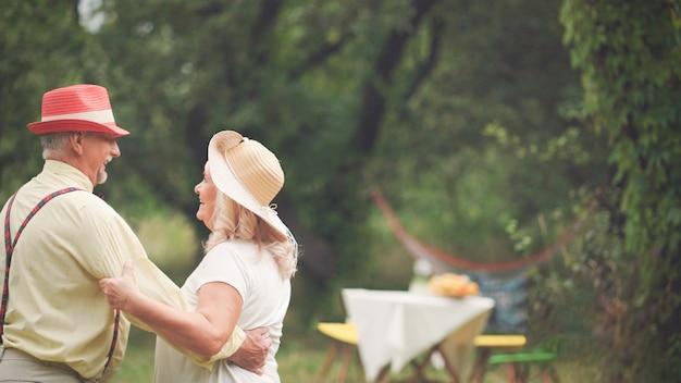 Danse d'un couple de personnes âgées dans le jardin d'été