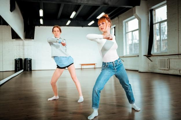 Danse énergique. belle danseuse professionnelle rousse portant un jean bleu et son élève se déplaçant énergiquement