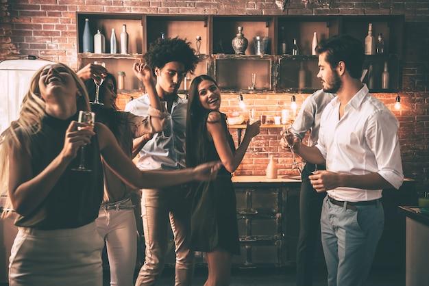 Danse insouciante avec des amis. jeunes joyeux dansant et buvant tout en profitant d'une fête à la maison dans la cuisine