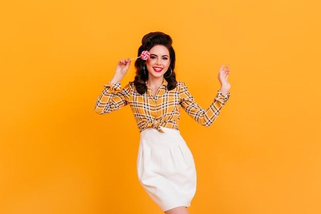 Danse de jeune femme avec une coiffure élégante tenant une sucette. photo de studio de pin-up en chemise à carreaux.