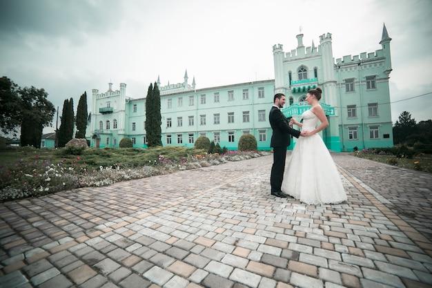 Danse les jeunes mariés avec un château en arrière-plan