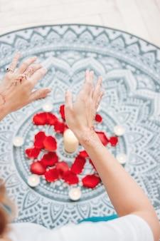 Danse des mains féminines avec mehendi sur l'autel des bougies et des pétales de rose, pratiques des femmes
