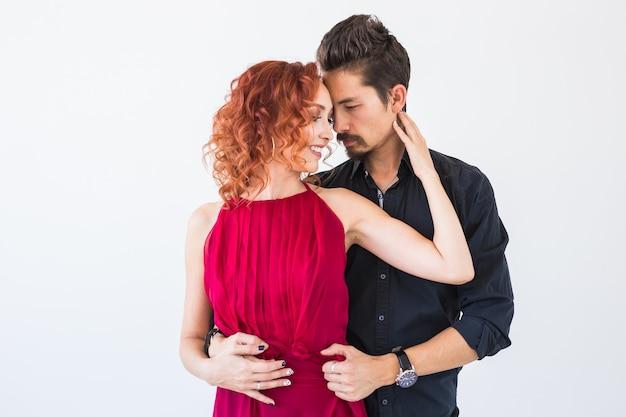 Danse sociale, bachata, kizomba, salsa, concept de tango - bouchent le portrait de femme homme vêtu de belles tenues sur un mur blanc.