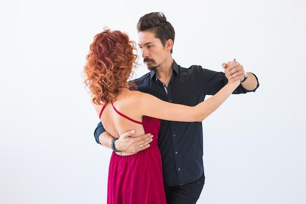 Danse sociale, bachata, kizomba, salsa, concept de tango - femme habillée en robe rouge et homme en costume noir sur mur blanc.