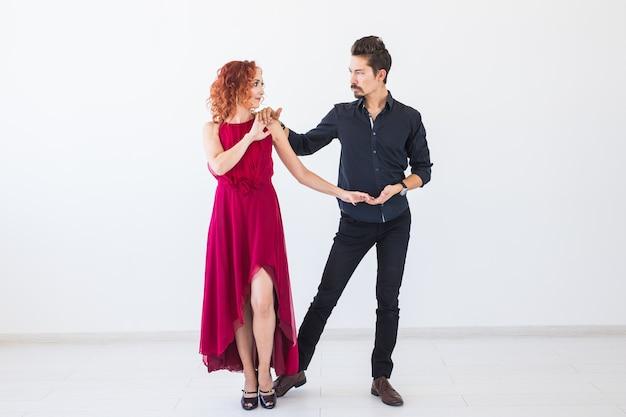Danse sociale, bachata, kizomba, salsa, concept de tango - femme vêtue d'une robe rouge et homme en costume noir sur un mur blanc.