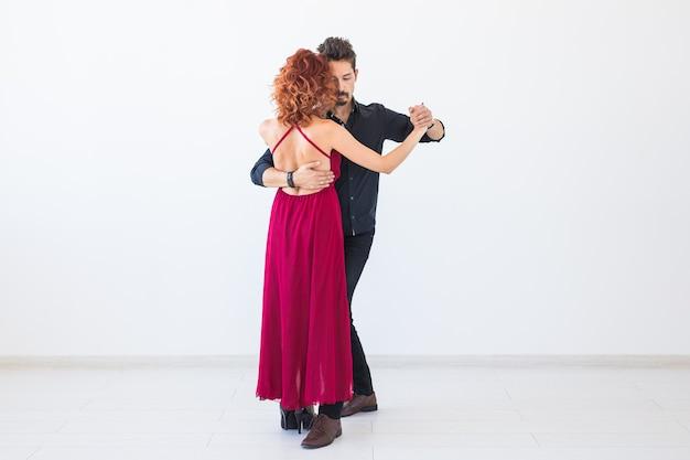 Danse sociale, tango, bachata, concept de kizomba - beau couple dansant sur un mur blanc avec espace de copie