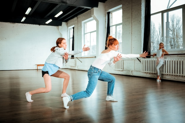 Danser dans le studio. belle danseuse professionnelle rousse portant un jean bleu et son élève dansant de manière expressive