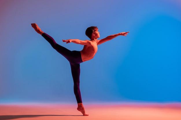 Danseur de ballet adolescent danse pieds nus sous une lumière colorée.